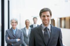 businessman smiling, three businesspeople behind